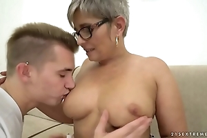 Grandma deepthroats a juvenile broad in the beam dick before riding greater than crimson